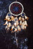 Dream catcher on black background in the smoke stock photography