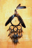 Dream catcher with eagle and raven feathers on orange structure wall.  royalty free stock images