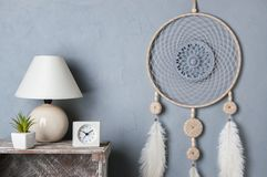 Dream catcher on gray. Gray beige dream catcher in bedroom interior on gray textured background. Bedroom decor Royalty Free Stock Photo