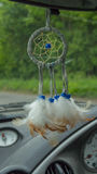 Dream catcher hanging in car. Driving down road Royalty Free Stock Photo
