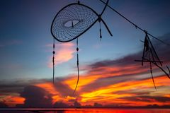 Dream catcher silhouette on colorful sunset background royalty free stock images