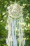 Dream catcher on a sunny green blurred background. Ethnic design, boho style, tribal symbol Royalty Free Stock Images