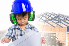 Dream of the child's future career  (engineer). Dream of the child's future career (engineer). Asian (thai) boy with blueprint, wearing earmuffs and blue helmet Royalty Free Stock Photo
