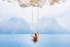 Dream concept, beautiful young woman on the swing. In fjord Norway, inspiring landscape royalty free stock photo