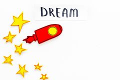 Dream concept. Hand lettering dream at white cosmos background with rocket and stars top view copy space Royalty Free Stock Photo