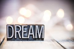 Dream Concept Vintage Letterpress Type Theme. The word DREAM written in vintage metal letterpress type on a bokeh light and wooden background royalty free stock image