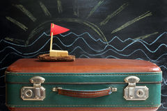 Dream of a cruise during the holidays. Old retro suitcase and ship with a red flag on a background of the sun and waves drawn in chalk on the blackboard Stock Images