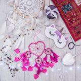 Unicorn sleep mask. Dream flatlay with a unicorn mask for sleeping and dreamcatchers from Dominican Republic and Spain, pink pillow from India and bracelet from Royalty Free Stock Photos
