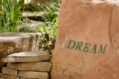 Dream garden. Large rock in outdoor garden with the words dream painted on it Stock Images