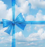 Dream Gift. From a fantasy wish list concept as an imaginary silk ribbon and bow on a sky background as a symbol of dreaming of holiday hopes for a merry Royalty Free Stock Photos