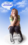 Dream Girl. A cute girl against a sky blue and clouds background, sits and wonders, with the word dream in the thought bubble over her head Royalty Free Stock Photography