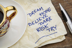 Dream, hope, believe. Dare, risk, try - motivational words - a napkin doodle with a cup of espresso coffee Stock Image