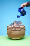 Dream about house. Dream about own house concept - man cultivate (water) own house in flowerpot and believe its growth. Blue and green background Stock Photos