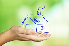Dream House Concept. Image of a hand holding house doodle image over green blur background Stock Image
