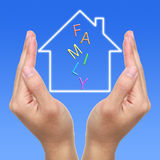 Dream House. Two hands and dream house with FAMILY on blue background stock images