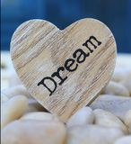Dream. An inspirational word painted onto a wooden heart - nestled in amongst white pebbles with a vivid blue background giving the image a seaside feel Royalty Free Stock Photography