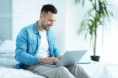 Joyful freelancer sitting on bed and working on laptop. Dream job. Positive minded young man smiling cheerfully while relaxing on a bed and typing on a laptop Stock Photos
