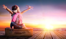 Dream journey - Little Girl On Vintage Suitcase. At Sunset royalty free stock images