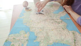 Dream of a journey. Map compass with a cup of tea on the table. A woman moves a toy plane along the route of her dreams. Desire to go on a trip. Video footage stock footage