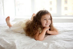 Dream the little princess on a white bed close-up. Royalty Free Stock Images