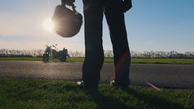 A dream and a motorcycle - biker looks at his bike. Biker holding a helmet on a motorcycle and looks at the sun stock video