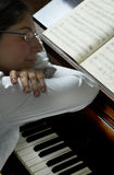 Dream Music. Pensive portrait of a piano teacher sitting at the piano, her arms crossed and leaning on the piano above the keyboard. Her face is resting on her stock photo