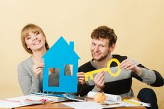 Happy couple dreaming about house. Dream and new plan for living. Young joyful smiling people thinking dreaming about their first house. Couple with big key to Stock Images