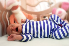 When the dream is over. Yawning baby in a wooden crib Stock Images
