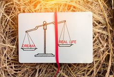 Dream and real life with scale on notebook Stock Photos