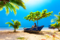 Dream scene. Young girl sitting in the boat under the palm trees Royalty Free Stock Photography
