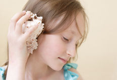 Dream About Sea. Girl is holding the sea shell near the ear Royalty Free Stock Images