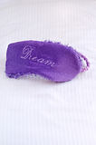 Dream Sleep Mask. The Dream purple sleep mask standing on a pillow background Royalty Free Stock Images