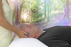 Dream State Spiritual healing session. Female hands laid gentle either side of a male patient`s head channeling healing energy with a beautiful woodland rainbow royalty free stock photo