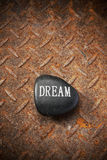 Dream Stone Background. A stone with the word dream on a rusty metal background Stock Image