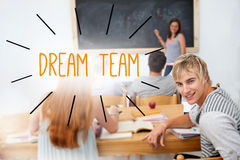 Dream team against students in a classroom Stock Photos