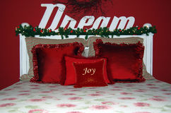 Christmas bed with red pillows and garland royalty free stock photos