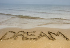 Dream Time. The word dream is carved in the sand on the shoreline in this conceptual photo Stock Images