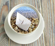 The dream of a travel. Is reflected in a cup. The ship is made of paper. The ship is on the beach Royalty Free Stock Photo