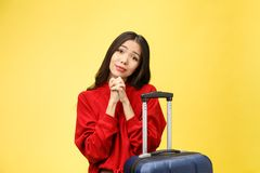 Dream about travel and vacation. Studio portrait of excited pretty young woman with praying hands. Isolated on yellow. stock image