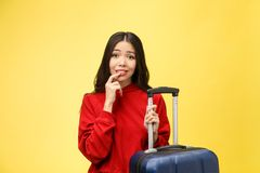 Dream about travel and vacation. Studio portrait of excited pretty young woman with praying hands. Isolated on yellow. stock photography