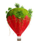 Dream traveling. Red hot-air balloon with green island on it Royalty Free Stock Image