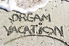 Dream vacation phrase handwritten on the beach Stock Photos
