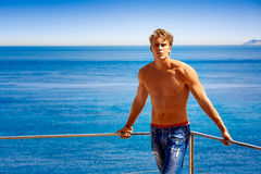 Dream Vacation by the Sea. Dream Vacation. Handsome blonde young man in jeans and shirtless sunbathe at the balcony with sea background Stock Photo