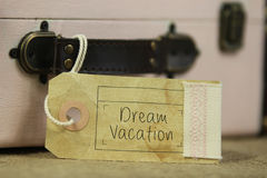Dream vacation tag on vintage suitcase. Paper tag with the handwritten words 'Dream vacation' on vintage suitcase Royalty Free Stock Photos
