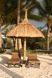 Dream Vacation for two. Honeymoon Scene: Two sunbeds on a tropical luxury hotel beach, underneath a wooden sunshade. Mauritius, Africa Stock Images