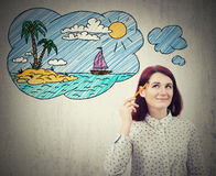 Dream of vacation. Young thoughtful businesswoman, holding a pencil pointed to face, drawing imaginary summer vacation sketch with a palm island and a boat on Royalty Free Stock Photo