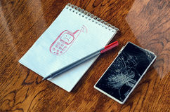 Dream, visualization desire, need a new phone concept. Freehand drawing of old phone in notebook. Smartphone with broken screen on wooden table. Dream Stock Photos