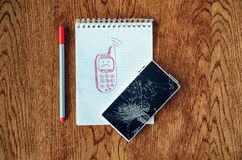 Dream, visualization desire, need a new phone concept. Freehand drawing of old phone in notebook. Smartphone with broken screen on wooden table. Dream Royalty Free Stock Image