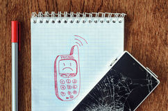 Dream, visualization desire, need a new phone concept. Freehand drawing of old phone in notebook. Smartphone with broken screen on wooden table. Dream Royalty Free Stock Images