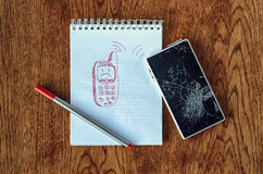 Dream, visualization desire, need a new phone concept. Freehand drawing of old phone in notebook. Smartphone with broken screen on wooden table. Dream Stock Photo